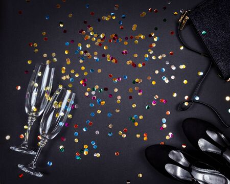 Set of women accessories romantic party creative composition. Shoes, decorations, glasses of champagne, gifts, gold colorful confetti on black background. Top view, flat lay, copy space Stok Fotoğraf