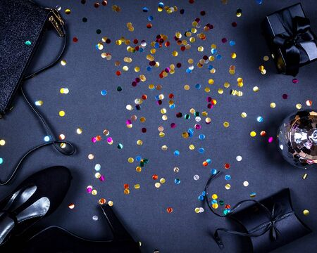 Set of women accessories romantic party creative composition. Shoes, decorations, gifts, gold colorful confetti on black background. Top view, flat lay, copy space Stok Fotoğraf