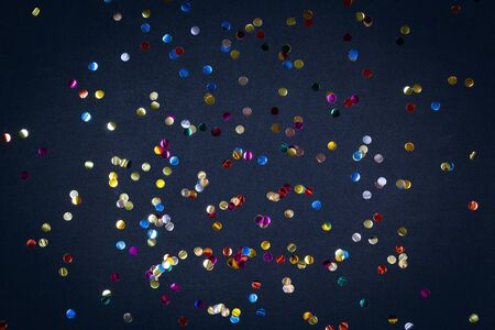 Gold colorful confetti of large size on black background. Festive backdrop of sparkles for birthday, carnival