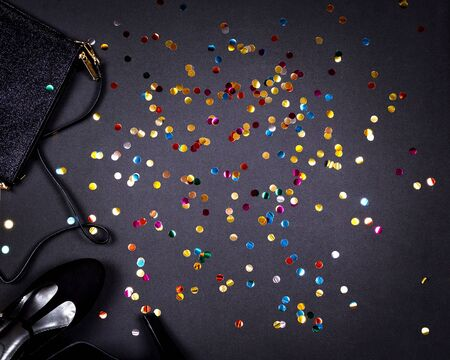 Set of women accessories romantic party creative composition. Shoes, decorations and gold colorful confetti on black background. Top view, flat lay, copy space Stok Fotoğraf
