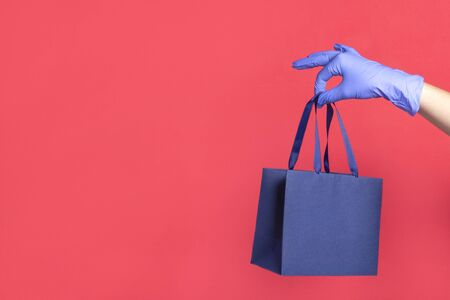 Woman hand in glove with gift paper bag on red background. Delivery of food, groceries, home shopping. Protection for COVID-19 Coronavirus precautions.