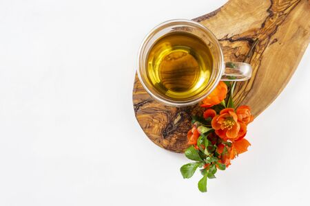 Glass cup of hot green tea with flowering quince apple tree branch on wooden stand on white background. Top view, flat lay, copy space