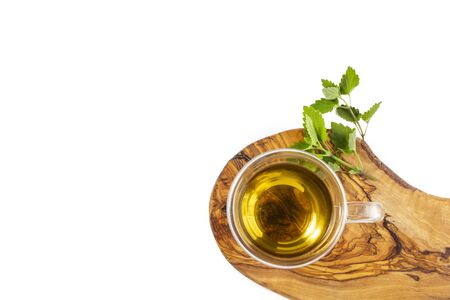 Glass cup of hot green tea with mint on wooden stand on white background. Top view, flat lay, copy space