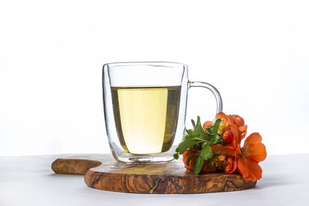 Glass cup of hot green tea with flowering quince apple tree branch on wooden stand on white background
