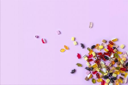 Colorful candy on pink background. Chewing sweets on light table. Top view, flat lay, copy space Standard-Bild
