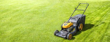 Lawn mower on fresh green lawn, freshly cut grass on summer sunny day, banner
