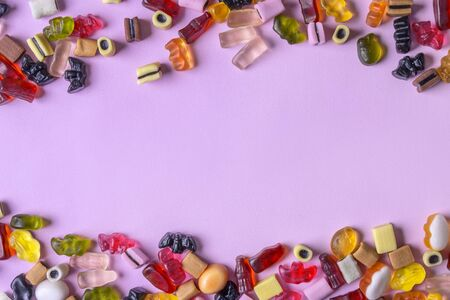 Colorful candy on pink background. Chewing sweets on light table. Top view, flat lay, copy space Stok Fotoğraf