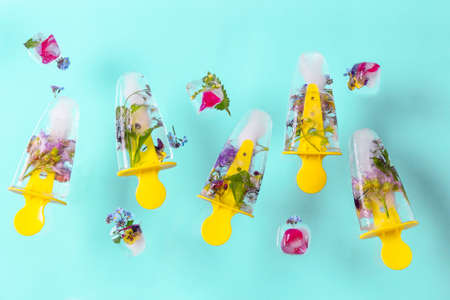 Flying ice-cream with flowers and ice cubes on blue pastel table. Fresh bright summer background. Standard-Bild