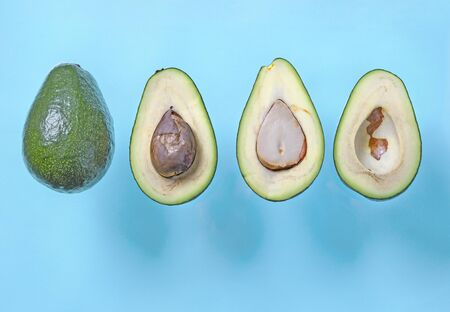 Fresh avocado halves with seed flying on blue background. Minimal concept organic summer food. Flat lay, top view, copy space Stok Fotoğraf