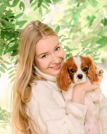 Portrait happy blonde girl with long hair holding cute Purebred puppy Cavalier King Charles Spaniel. Tree leaves on summer morning in light outdoors sun with natural blurry background, close-up