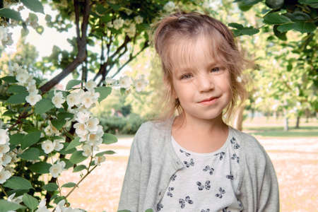 Portrait of beautiful little girl 4-7 years old with blue-green emerald eyes in flowering spring summer park on natural background