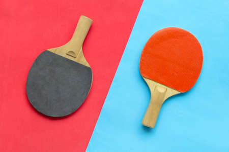 Red and black rackets for table tennis on blue and red background. Banque d'images