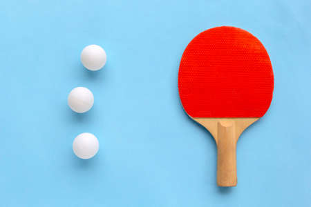 Red racket for table tennis with white balls on blue background. Banque d'images
