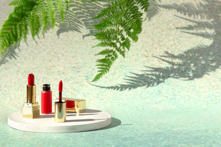Red lipstick and lip varnish on light background of nature with fern leaves. Decorative beauty cosmetic products for woman