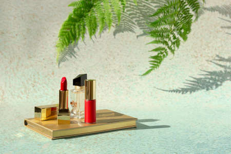 Red lipstick, perfume and lip varnish on light background of nature with fern leaves. Decorative beauty cosmetic products for woman