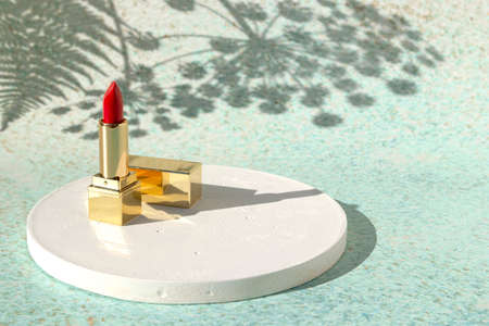 Red lipstick on light background of nature with shadow from flowers. Decorative beauty cosmetic products for woman