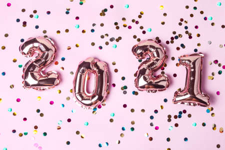 Gold pink balloons in form of numbers 2021 with colorful shiny confetti on pink background. Happy New Year celebration. Flat lay, top view 스톡 콘텐츠 - 153365122