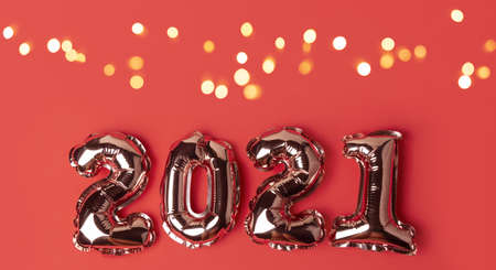 Happy New Year 2021 celebration. Gold balloons in form of numbers with shiny bokeh lights on festive on red background. Flat lay, top view, banner Stock fotó