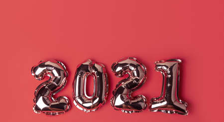 Happy New Year 2021 celebration. Gold balloons in form of numbers on red background. Flat lay, top view, banner Stock fotó