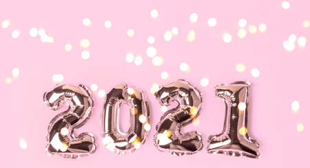 Happy New Year 2021 celebration. Gold balloons in form of numbers with shiny bokeh lights on festive on pink background. Flat lay, top view, banner Stock fotó