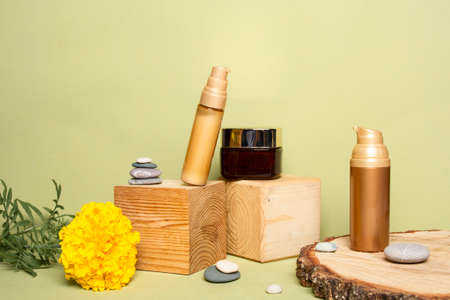 Organic cosmetic concept. Mock up of natural creams in golden bottles on forest materials. Decorative eco beauty products for woman.