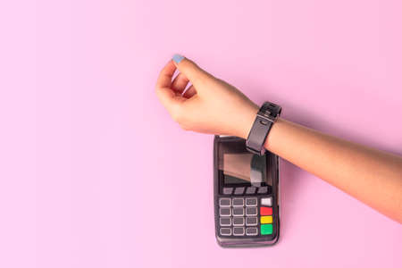 Payment for purchases using smart watches and POS terminal on light pink background. Contactless payment with NFC tecnology Stock fotó