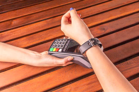 Payment for purchases using smart watches and POS terminal on wooden background. Contactless payment with NFC tecnology