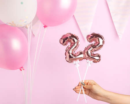 Decoration for birthday party. Female hand holding golden balloon in form of 22 number on pink background.