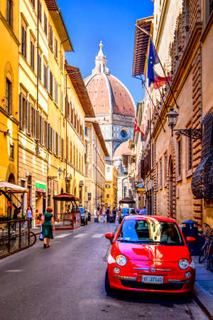 Red small car is parked in narrow street of Florence with view of Basilica Santa Maria del Fiore, Florence, Tuscany, Italy.