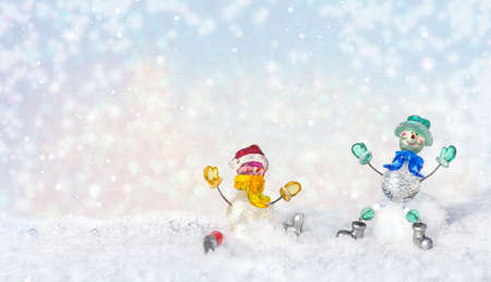 Funny snowmen carefree on snow in winter new year landscape. Beautiful bokeh circles Christmas snowy background, banner format, copy space. Stock fotó