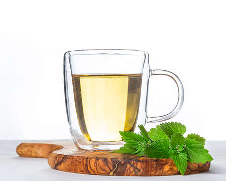 Glass cup of hot green tea with mint on wooden stand on white background. Stock fotó