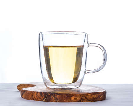Glass cup of hot green tea on wooden stand on white background.
