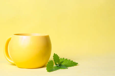 Yellow cup of hot tea with mint on yellow background. Stock fotó