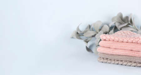 Pile of pink knitted cashmere scarves, sweaters on light blue background. Folded autumn and winter clothing with eucalyptus leaves branch, banner Stock fotó