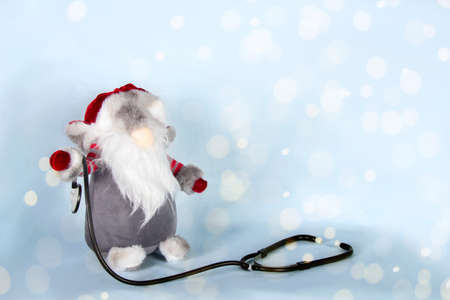 Santa Claus with stethoscope on party. Christmas medical blurred lights background. Concept of new year clinic, banner