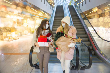 Young women in medical mask shopping for Christmas in mall. Xmas holidays in new Covid-19 reality. Selective focus.