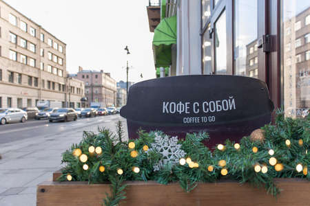 Street cafe sign - Coffee to go with Christmas lights and decorations. City life on street in early morning