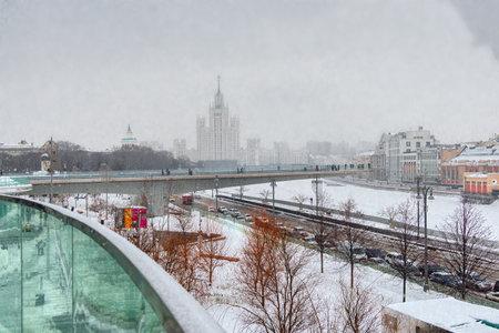 Moscow, Russia - February 21, 2021: Floating pedestrian bridge in Zaryadye Park above Moskva River, Kotelnicheskaya Embankment Building in snowy winter, Moscow, Russia 新聞圖片