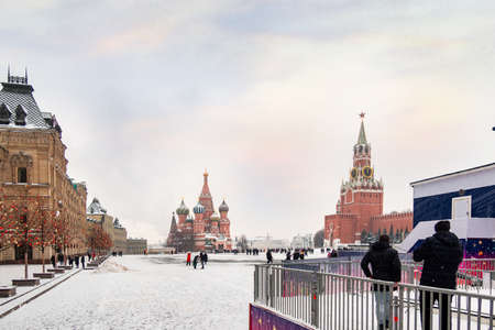Moscow, Russia - February 21, 2021: Moscow Kremlin with Spassky Tower and Saint Basil's Cathedral in center city on Red Square in snowy winter, Moscow, Russia.