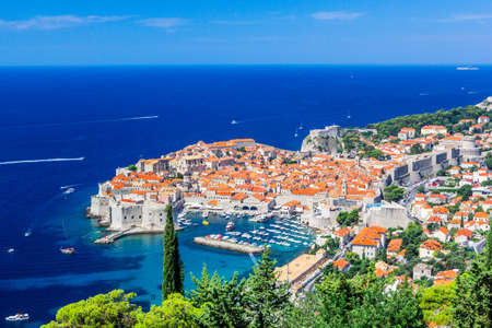 Panoramic view of Old Town medieval Ragusa and Dalmatian Coast of Adriatic Sea in Dubrovnik. Blue sea with white yachts, beautiful landscape, aerial view, Dubrovnik, Croatia.