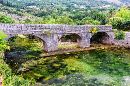 Old stone bridge over small transparent river at foot of mountains, near Risana, Boca-kotor bay, Montenegro.