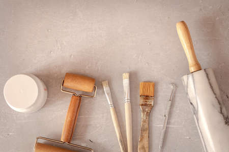 Professional working tools for working with clay, plasticine. Pottery shovels, brushes, rolling pin on marble table. Flat lay, top view.