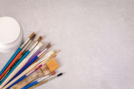 Professional dirty working artist brushes and paint on marble table. Flat lay, top view.