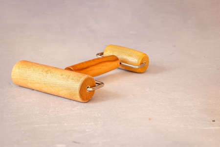 Wooden double-sided roller for rolling out dough or clay on marble table. Professional working tool. High quality photo 版權商用圖片