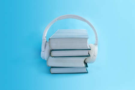 Wireless white headphones on stack of books on light blue background. Concept for audiobooks in minimal style.