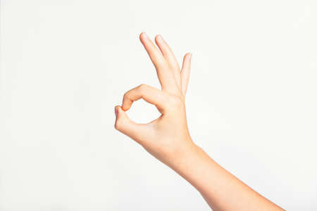 Woman's hand gesturing good or sign OK on light gray background.