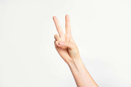 Woman's hand gesturing peace sign or victory on light gray background.