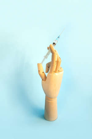 Wooden human hand with syringe with vaccine for disease on light blue background. Doctor holds syringe with medical injection. Health care and disease prevention concept. Vertical photo.