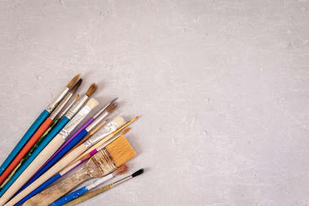 Professional dirty working artist brushes on marble table. Flat lay, top view.