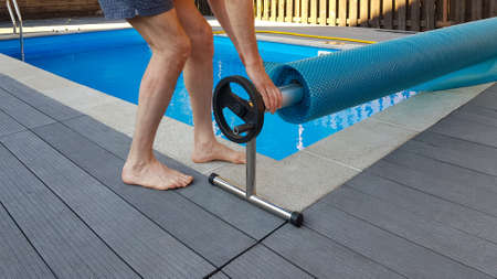 Man covers swimming pool with cover for protection against dirt, leaves, heating and cooling water